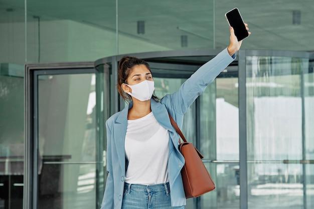Kobieta z maską medyczną i smartfonem przywołuje taksówkę na lotnisku podczas pandemii