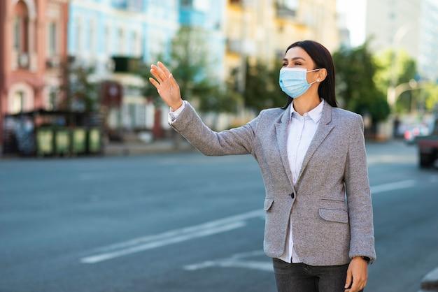 Kobieta Z Maską Medyczną Macha Na Ulicy Premium Zdjęcia