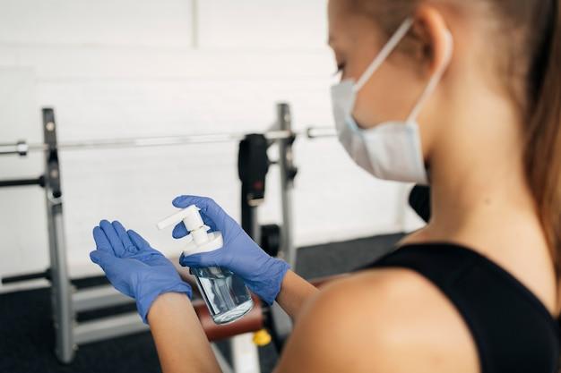 Kobieta z maską medyczną na siłowni za pomocą środka dezynfekującego do rąk