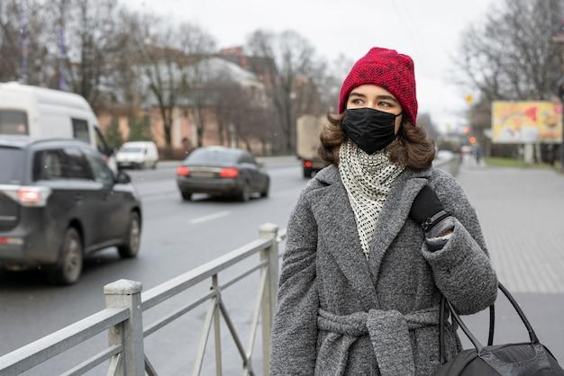 Kobieta z maską medyczną na zewnątrz w mieście
