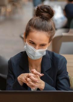 Kobieta z maską medyczną o rozmowie wideo