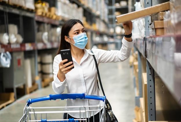 Kobieta z maską medyczną patrząc na swój telefon komórkowy i zakupy w magazynie podczas pandemii koronawirusa