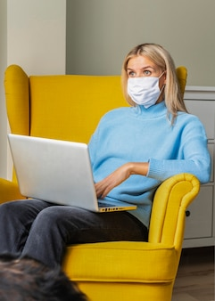 Kobieta z maską medyczną pracuje na laptopie w domu podczas pandemii