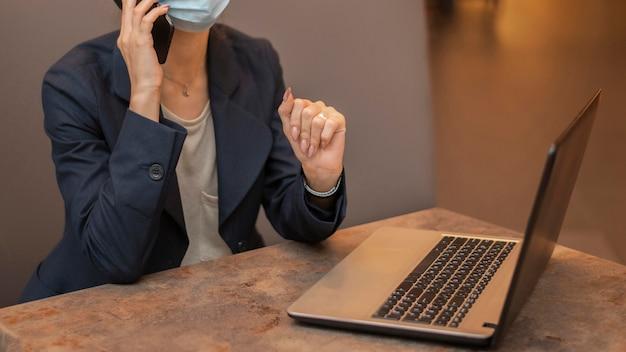 Kobieta z maską medyczną pracuje na laptopie