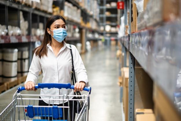 Kobieta z maską medyczną szuka i robi zakupy w magazynie podczas pandemii koronawirusa