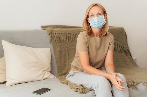Kobieta z maską medyczną w domu podczas kwarantanny