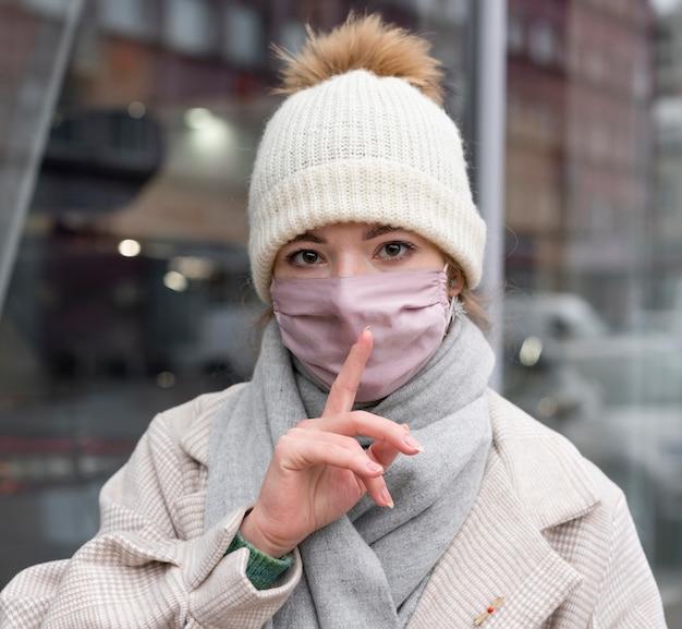 Kobieta z maską medyczną w mieście domagająca się ciszy
