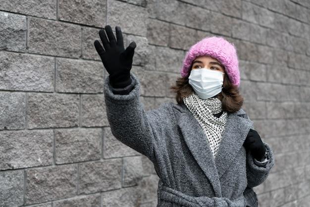 Kobieta z maską medyczną w mieście macha