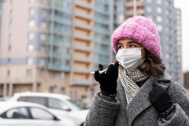 Kobieta z maską medyczną w mieście rozmawia przez telefon