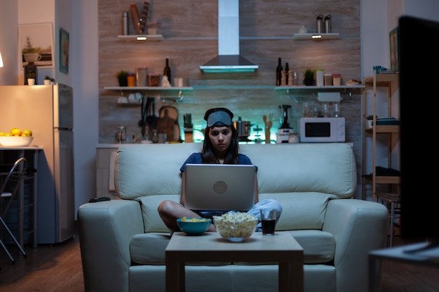 Kobieta z maską na oczy przy użyciu laptopa w nocy podczas oglądania telewizji i jedzenia przekąsek. szczęśliwa osoba w piżamie siedząca na kanapie, czytająca, pisząca, przeszukująca przeglądanie na notebooku za pomocą internetu, sprawdzająca pocztę