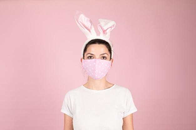 Kobieta z maską na sobie opaskę uszy królika wielkanocnego. wielkanoc podczas kwarantanny koronawirusa