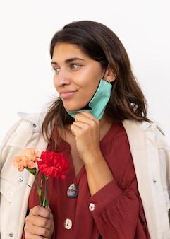 Kobieta z maską na twarz i kwiatami