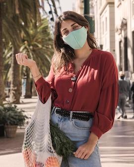 Kobieta z maską na twarz na zewnątrz trzymając torbę na zakupy