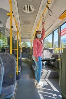 Kobieta z maską na twarz podróżująca po mieście autobusem