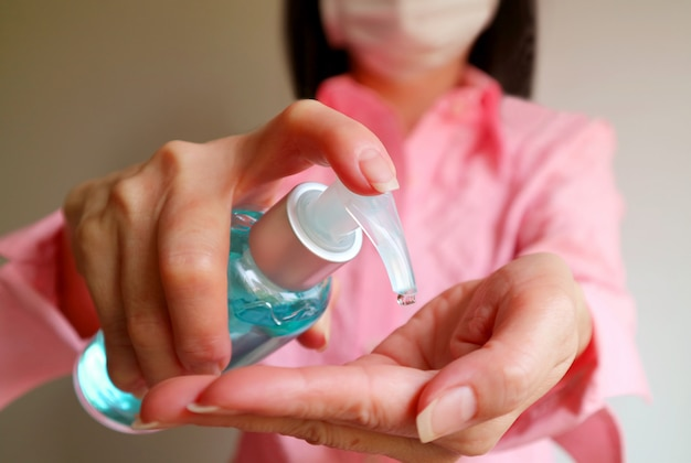 Kobieta z maską na twarz trzymająca alkoholowy żel do mycia rąk do wycierania rąk, aby zapobiec infekcji