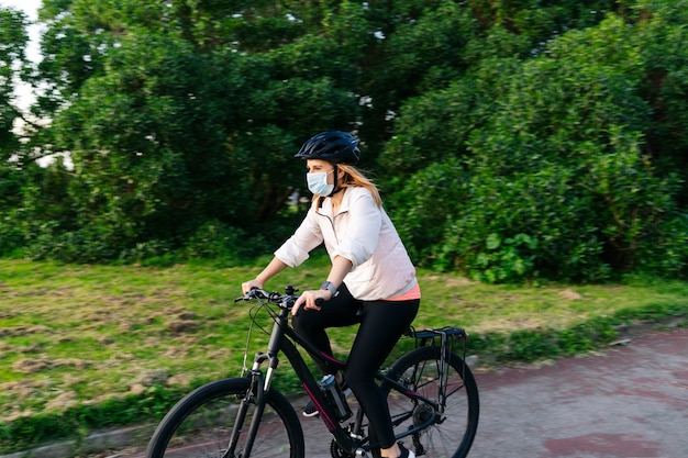 Kobieta z maską na twarzy na rowerze w mieście.