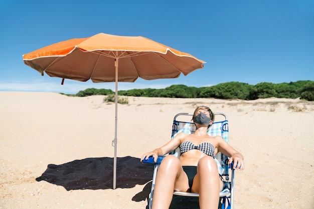 Kobieta z maską na twarzy na wakacjach leżąca w słońcu na leżaku na plaży tuż obok pomarańczowego parasola w środku pandemii koronawirusa