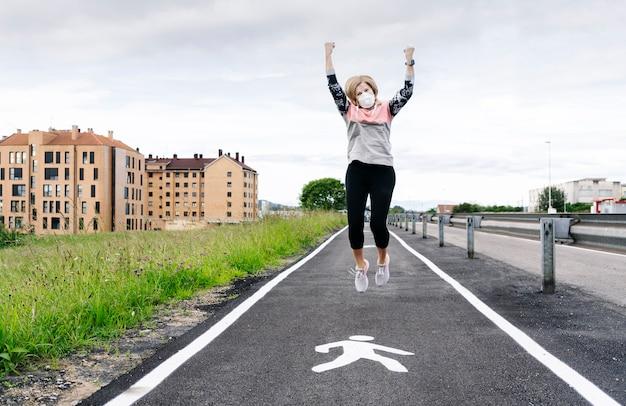 Kobieta z maską na twarzy podskakuje z radości, wychodząc na zewnątrz po kwarantannie