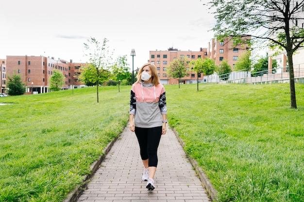 Kobieta z maską na twarzy przechodzi przez park z budynkami