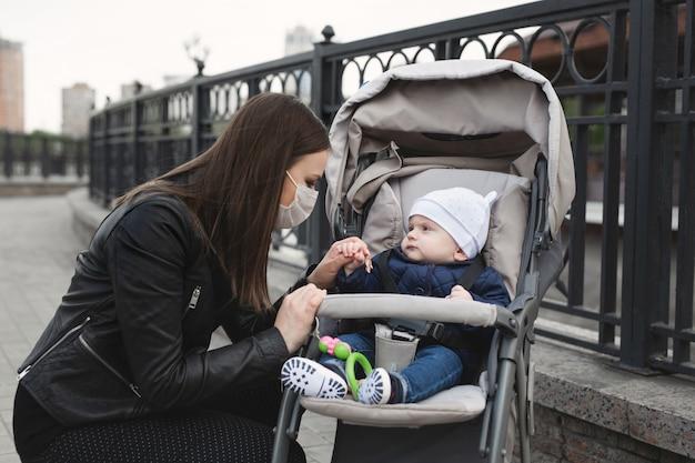 Kobieta z maską na twarzy w celu ochrony przed koronawirusem, covid-19 trzyma za rękę swoje małe dziecko, które siedzi w wózku