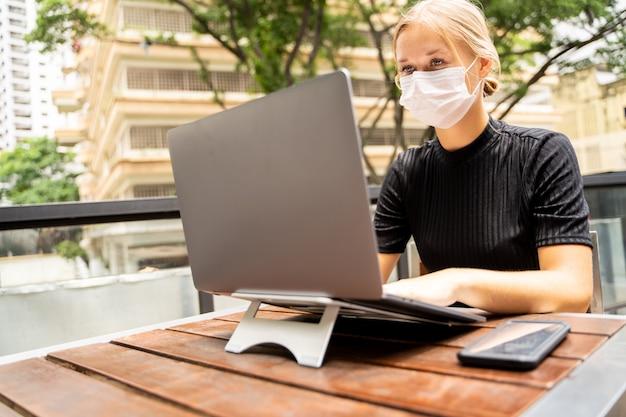 Kobieta z maską ochronną dla wirusa pracującego zdalnie ze swoim laptopem