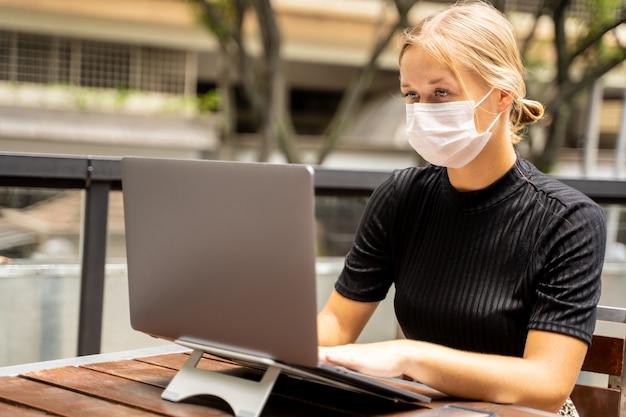 Kobieta z maską ochronną na twarzy pracy zdalnie ze swoim laptopem