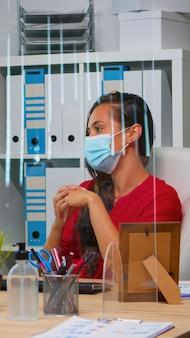 Kobieta z maską ochronną po konferencji online spotkanie w nowoczesnym nowym normalnym biurze. freelancer pracujący w miejscu pracy na czacie z zespołem zdalnym podczas wirtualnego webinaru z wykorzystaniem technologii internetowej
