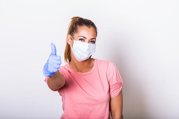 Kobieta z maską ochronną pokazuje kciuk up i patrzeje kamerę.