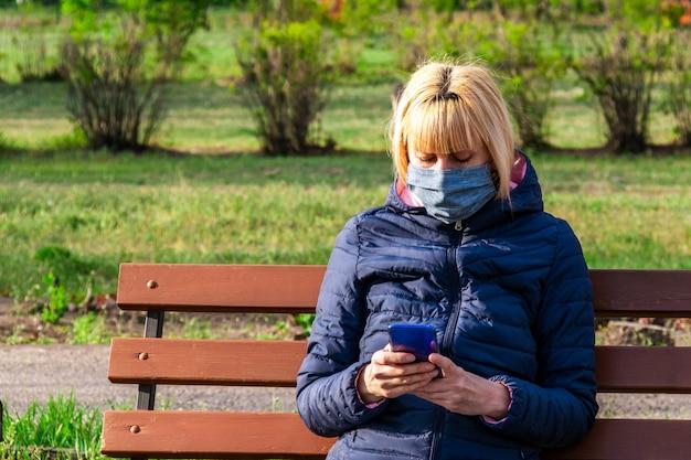 Kobieta z maską ochronną używać mądrze telefon w parku, coronavirus pojęcie