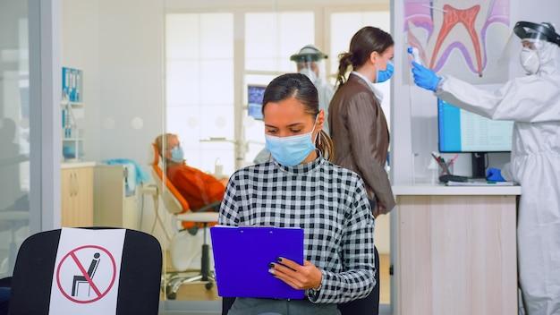 Kobieta z maską ochrony twarzy pisanie na formularzu rejestracyjnym w klinice stomatologicznej, siedząca w recepcji z poszanowaniem odległości społecznej. dentysta pracujący w kombinezonie w klinice dentystycznej z nową normalną