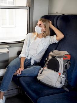 Kobieta z maską podróżuje z pociągiem