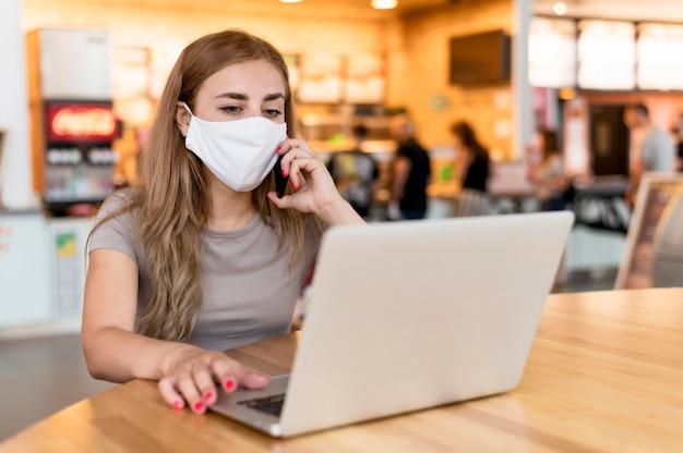 Kobieta z maską pracuje na laptopie na tarasie