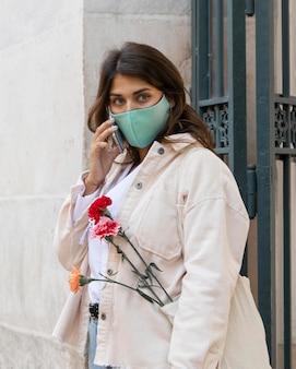 Kobieta z maską rozmawia przez telefon na zewnątrz
