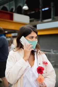 Kobieta z maską rozmawia przez telefon trzymając kwiaty