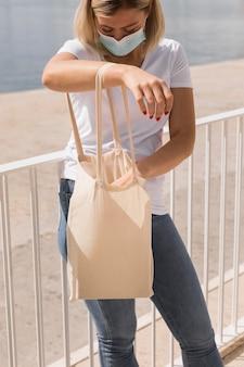 Kobieta z maską trzyma białą torbę na zakupy obok jeziora