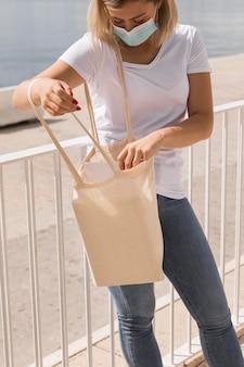 Kobieta z maską trzymając na zewnątrz białą torbę na zakupy
