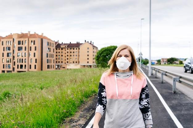 Kobieta z maską w każdym przechodzi przez deptak w mieście