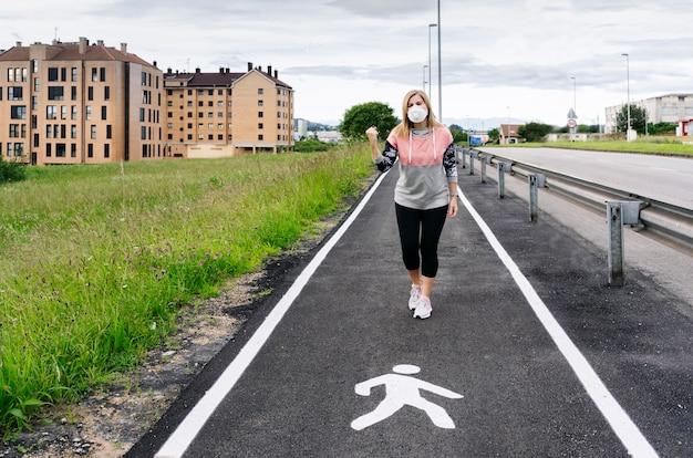 Kobieta z maską w każdym z nich idzie przez miasto z gestem zwycięstwa