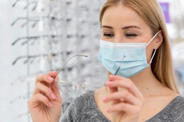 Kobieta z maską w sklepie przymierza okulary
