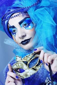 Kobieta z maską w twórczy obraz teatralny.