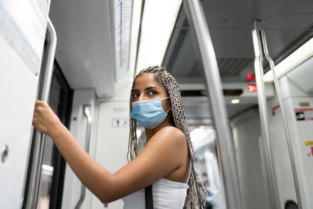 Kobieta z maską w wagonie metra