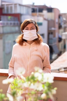 Kobieta z maską zamkniętą w domu, biorąc powietrze na tarasie