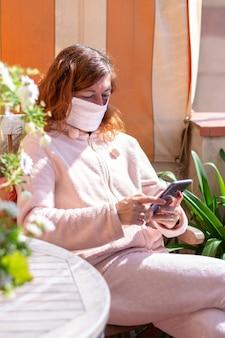 Kobieta z maską zamkniętą w domu z telefonem komórkowym