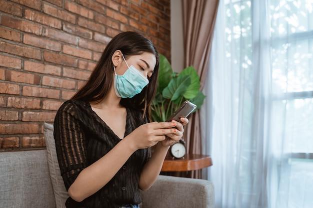 Kobieta z maskami używa telefon komórkowego dla ogólnospołecznego dystansowania