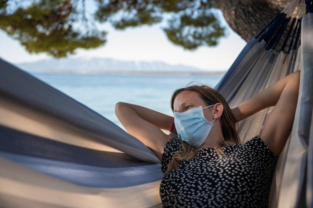 Kobieta z medyczną maską ochronną relaksującą w hamaku nad morzem