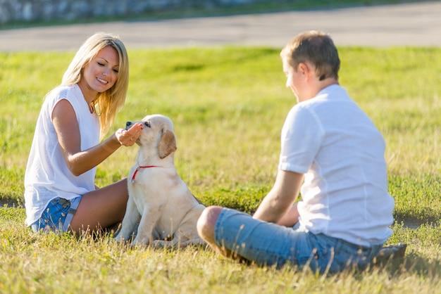 Kobieta z mężczyzna bawić się z labradora szczeniakiem w parku na trawie w wiośnie