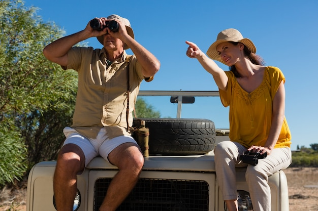 Kobieta z mężczyzną wskazując siedząc na pokrywie pojazdu