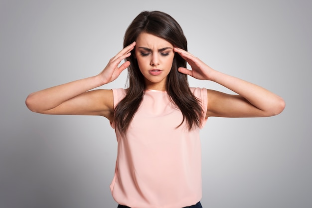 Kobieta z migreną masująca skronie