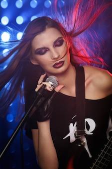 Kobieta z mikrofonem i gitarą w ręku na scenie śpiewa piosenkę w stylu rockowym
