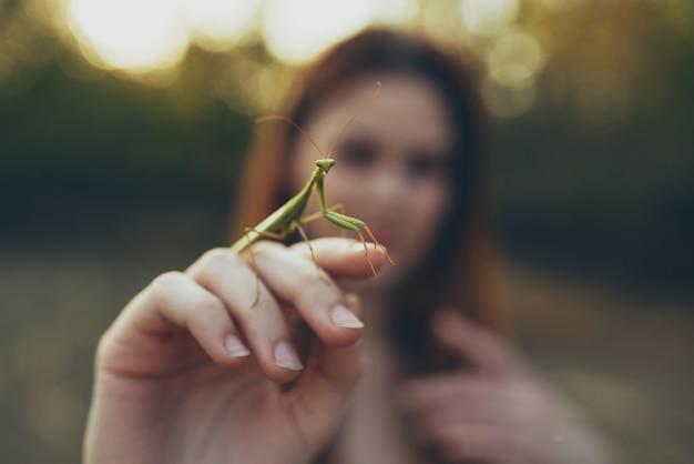 Kobieta z modliszki w ręku spacer natury. zdjęcie wysokiej jakości